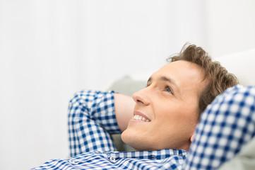 Happy Man Daydreaming On Sofa