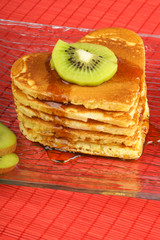 Stack of heart-shaped pancakes with syrup and kiwi fruit