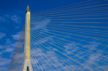 Fragment of a cable stayed bridge on blue the sky background.