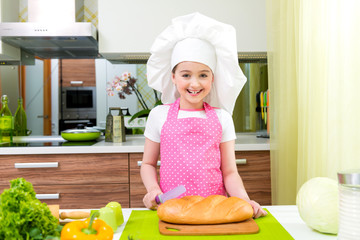 Little girl in pink apron cutting bread.