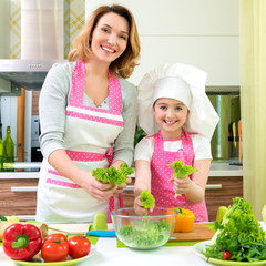 Smiling mother and daughter cooking a salad.