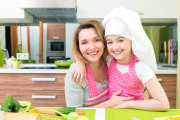 Happy mother and daughter in pink apron.