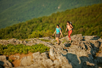Two women is trekking in the Crimea mountains with backpacks