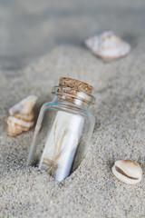 Mensaje en una botella de cristal en la arena de la playa