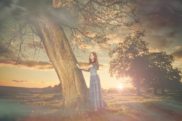 lady in blue dress at spring meadow tree sunset