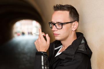 Closeup portrait of handsome smoking young man