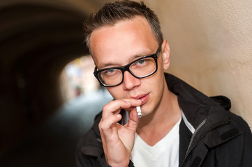 Portrait of young man smoking a cigarette in the street.