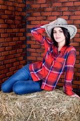 Girl cowboy sitting on the hay and keeps his hat on his head