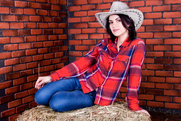 cowboy girl sits on hay in a plaid shirt and jeans