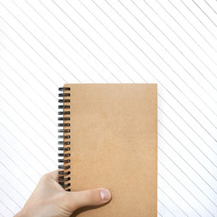 craft vertical blank notebook in man hand and wooden background