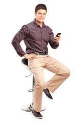 Man sitting on chair and holding cell phone