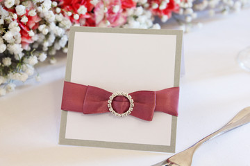 Ornate table name card with pink ribbon and place for your text.