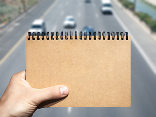 craft blank notebook in hand and traffic background