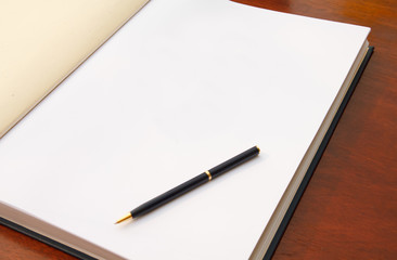 Large open book on wood table with white blank page and pen.