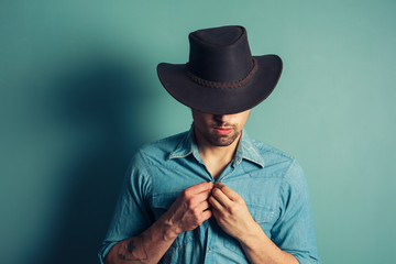 Cowboy buttoning his shirt