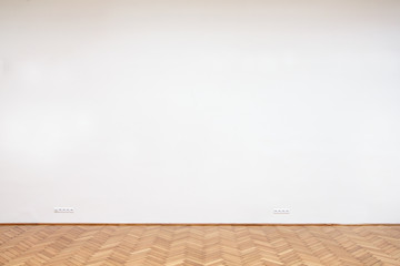 Large white wall with wooden floor tiles