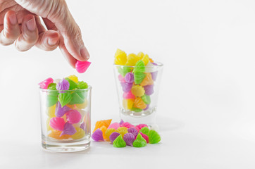Hand and 2 glass of colorful sweets
