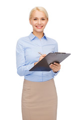 smiling businesswoman with clipboard and pen