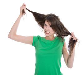 Wütende junge Frau mit kaputten Haaren isoliert in Grün