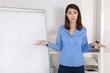 Hilflose junge business Frau steht vor einer Flip Chart