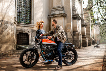 Loving couple near the motorcycle in the old city, general plan