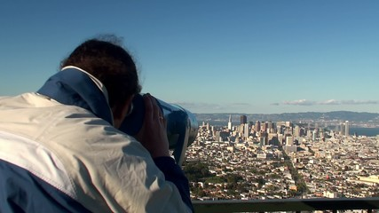 Tourist is looking through a telescopic viewer of San Francisco
