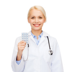 smiling female doctor with pills