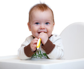 Smiling baby with spoon in his hands