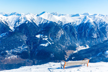 Bench in ski resort Bad Gastein in winter snowy mountains