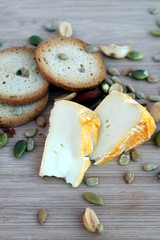 Cheeze snack with crackers and mixed nuts on a wooden board