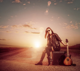 woman with guitar at sunset road