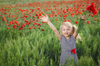 Little girl on the poppy meadow