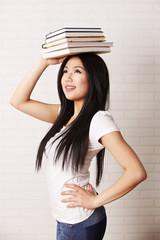 Studentin ballanciert Bücher auf dem Kopf