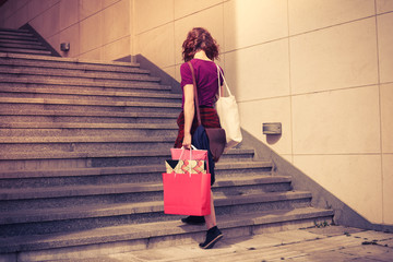Young woman with shopping walking up stairs