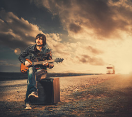 young man with guitar at sunset road