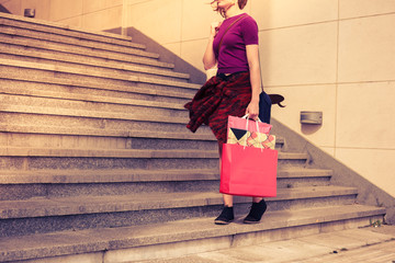 Young woman with shopping bags by stairs at sunset