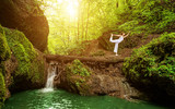 Fototapety Woman practices yoga in nature, the waterfall.