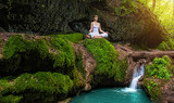Fototapety Woman practices yoga in nature, the waterfall. sukhasana pose