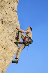 Extreme rock climbing, man on natural wall with blue sky.