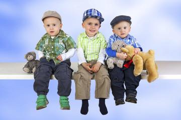 Three sitting boys with toys