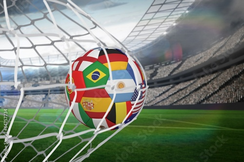 canvas print picture Football in multi national colours at back of net