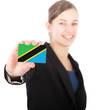 business woman holding a card with the flag of Tanzania