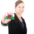 business woman holding a card with the flag of Wales