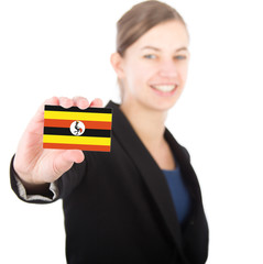 business woman holding a card with the flag of Uganda