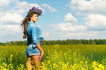 Beautiful young brunette in shorts and chaplet in a yellow field