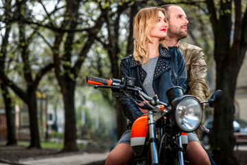 Couple sitting on the motorcycle in the city park