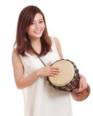 Asian woman playing a djembe