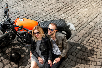 Couple lying on the paving near the motorcycle