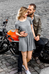 Couple standing and holding hands near their motorcycle
