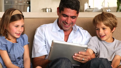 Cute children using tablet pc with father on couch